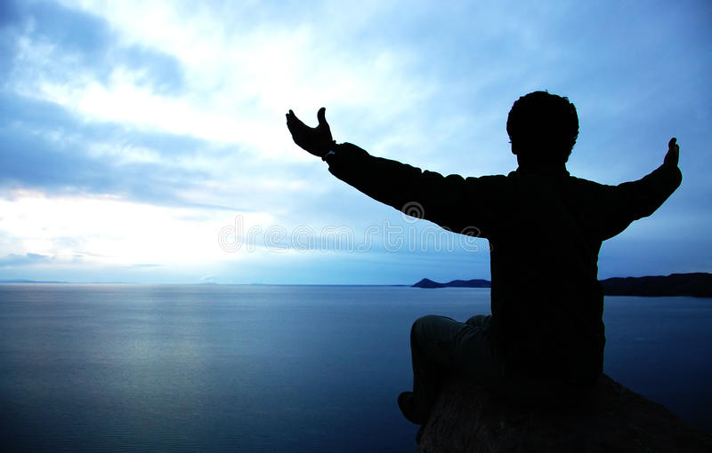 Creation. A man spreading his arms against the sky overlooking a huge lake