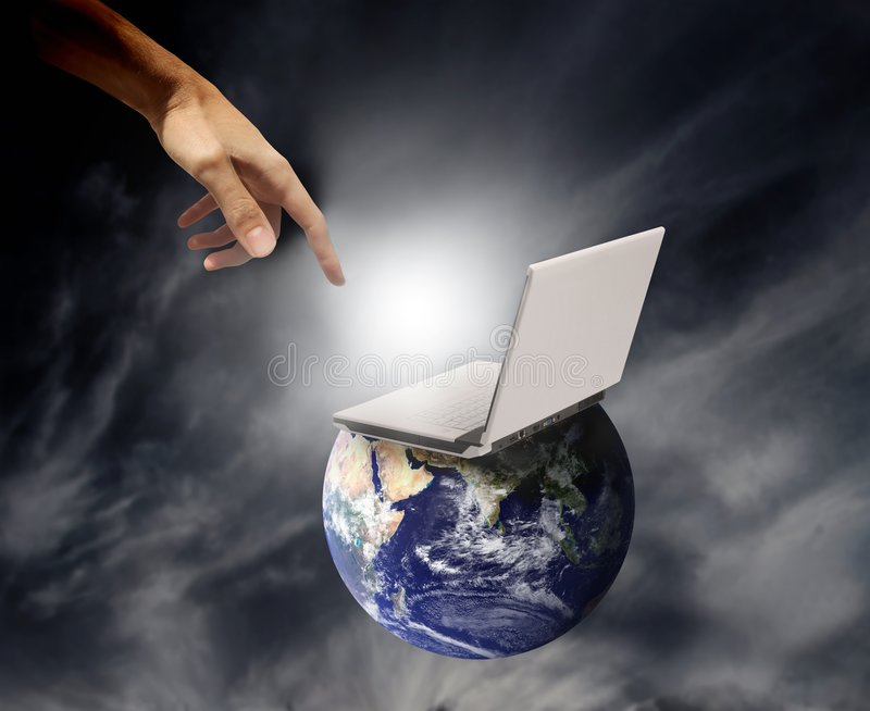 Creation. An hand touching a laptop leaning on a world stock photo
