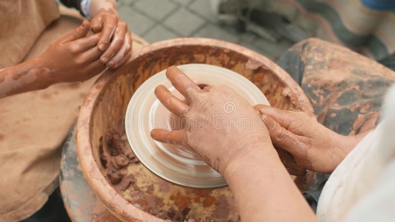 Creation covers a clay pot. Close up of hands working clay on potter`s wheel stock photo
