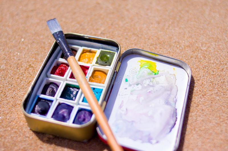 Artistic equipment: paint brushes, watercolors paintings on sand background at sunny summer day - creation, drawing and freedom co. Creation, drawing and freedom stock image