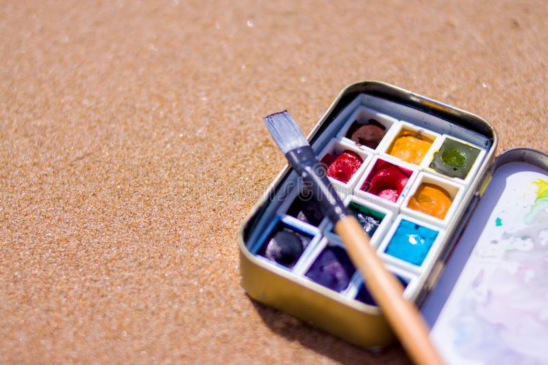 Artistic equipment: paint brushes, watercolors paintings on sand background at sunny summer day - creation, drawing and freedom co. Creation, drawing and freedom royalty free stock photos