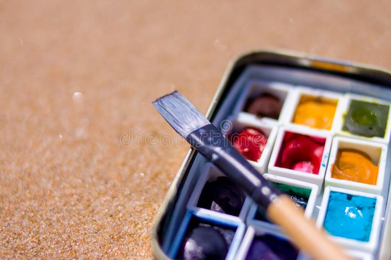 Artistic equipment: paint brushes, watercolors paintings on sand background at sunny summer day - creation, drawing and freedom co stock photo