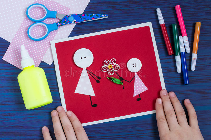 Creation a greeting card for the Mother`s Day by the child. Step royalty free stock photo