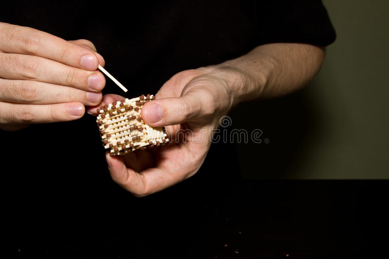Creation house of matches. Step by step. Handmade. Work at the table, dark background royalty free stock photo