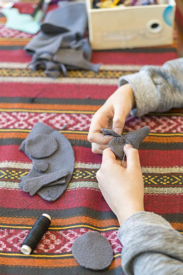 Creation. little girl sews toy made of felt. Little girl sews a gray mouse. Little girl sews a toy. vertical photo.  royalty free stock photos