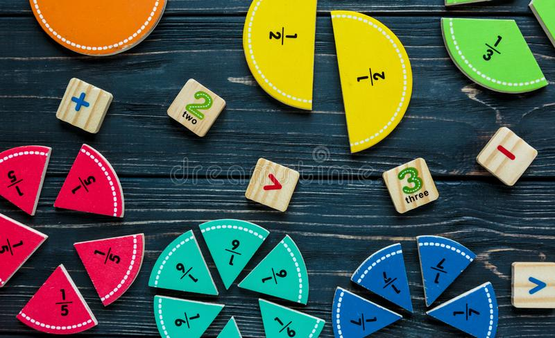 Creative Ð¡olorful math fractions on dark background. Interesting funny math for kids. Education, back to school concept stock photography