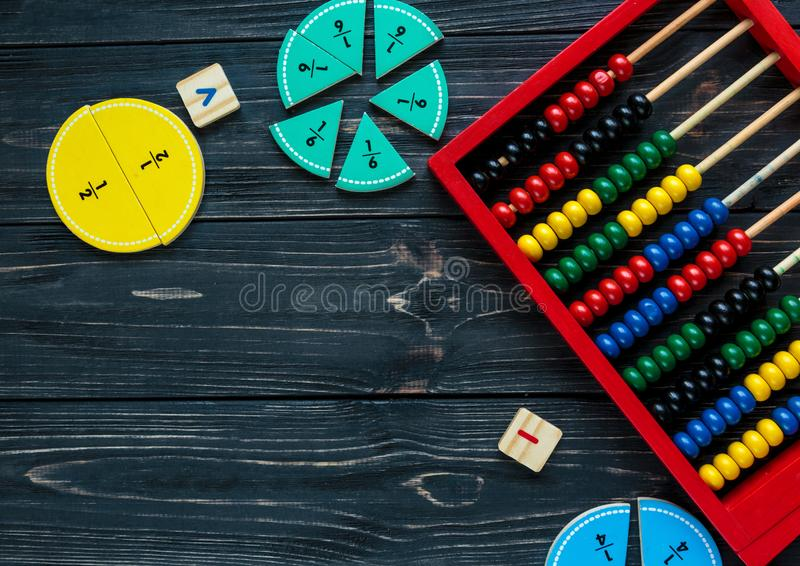 Creative Ð¡olorful math fractions on dark background. Interesting funny math for kids. Education, back to school concept. Geometry and mathematics materials royalty free stock images