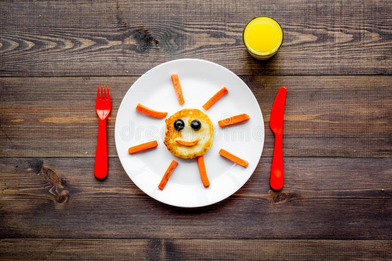 Creative approach to kid`s braekfast. Meal with cheesecake in shape of sun. Dark wooden background top view stock photos