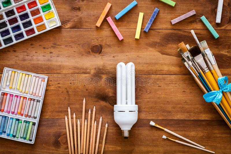 Creative art idea fantasy imagination concept, light bulb, paint brushes, paintbox with watercolors, crayons and pencils on brown royalty free stock images