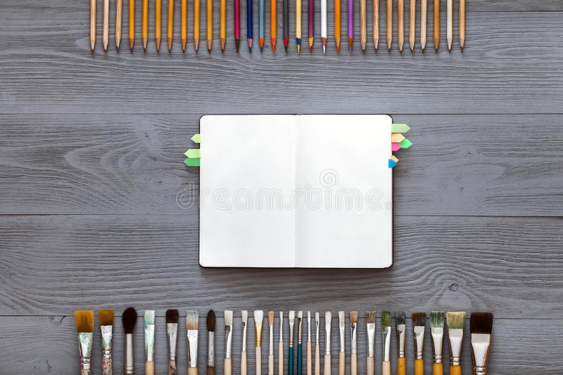 Creative art table concept, blank notebook sketchbook on grey wooden background royalty free stock photo