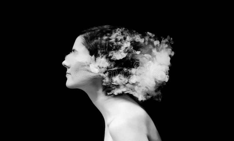 Creative of art woman portrait and smoke in face. black in white portrait and smoke on black background. Creative of art woman portrait and smoke in face. black royalty free stock image