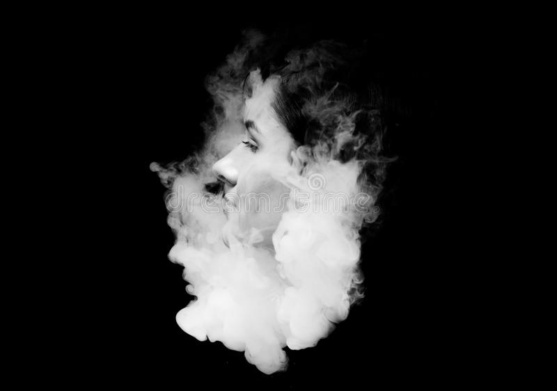 Creative of art woman portrait and smoke in face. black in white portrait and smoke on black background. Creative of art woman portrait and smoke in face. black royalty free stock images