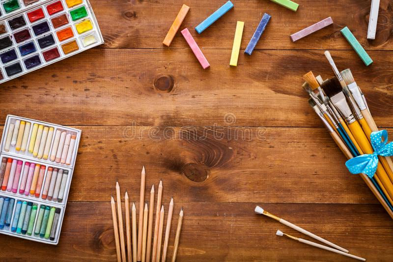 Creative art work accessories tools supplies set on messy desk, paint brushes, paintbox watercolors crayons pencils on brown. Wooden artistic background, back stock image