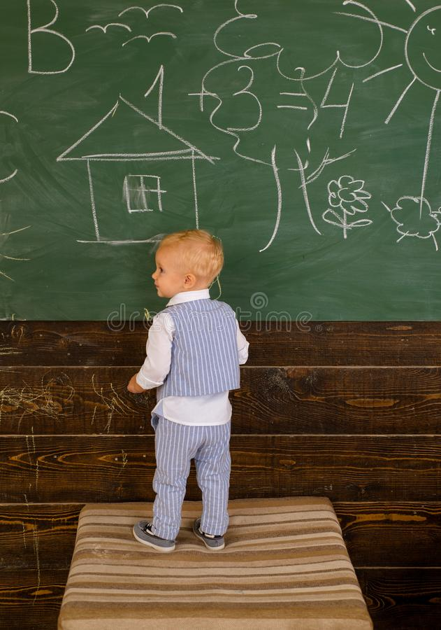 Creative artist painting doodle on classroom chalkboard. Little artist boy creating picture on school day. I was created stock photography