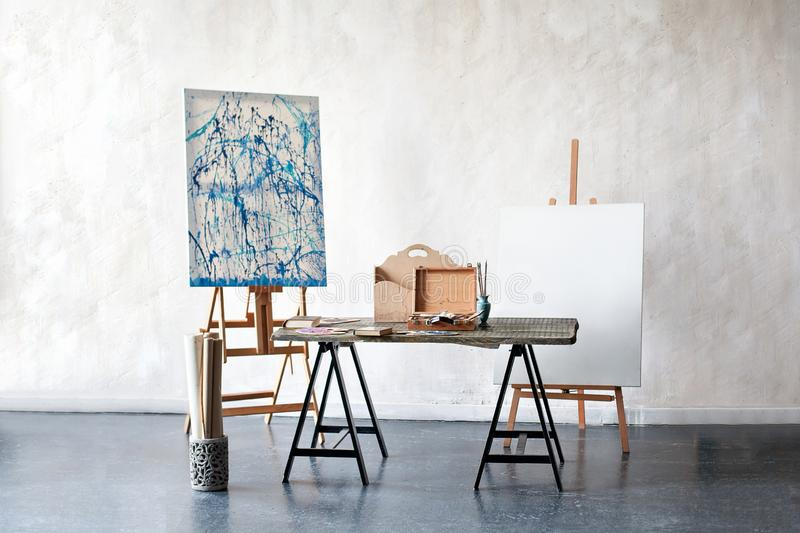 Creative artist workplace no people hobbies. Painting Studio of a freelance artist. Easel, canvas, brushes, pencils, paints with a royalty free stock photos