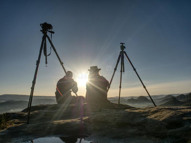 Creative artists stay at own cameras on tripods.  Hikers and enthusiasts. Creative artists stay at own cameras on tripods.  Hikers and photo enthusiasts work stock photo