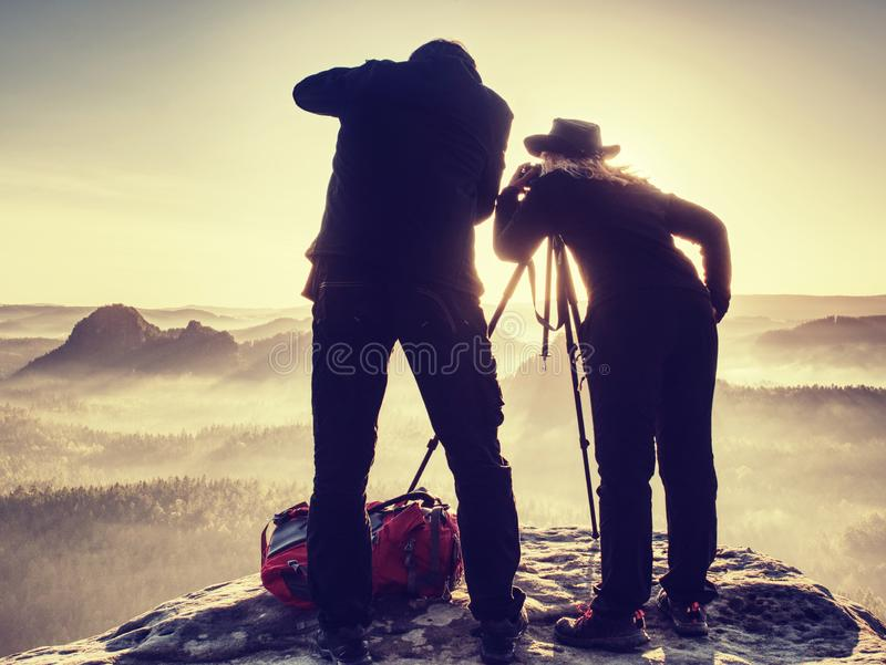 Creative artists stay at own cameras on tripods.  Hikers and enthusiasts. Creative artists stay at own cameras on tripods.  Hikers and photo enthusiasts work royalty free stock image