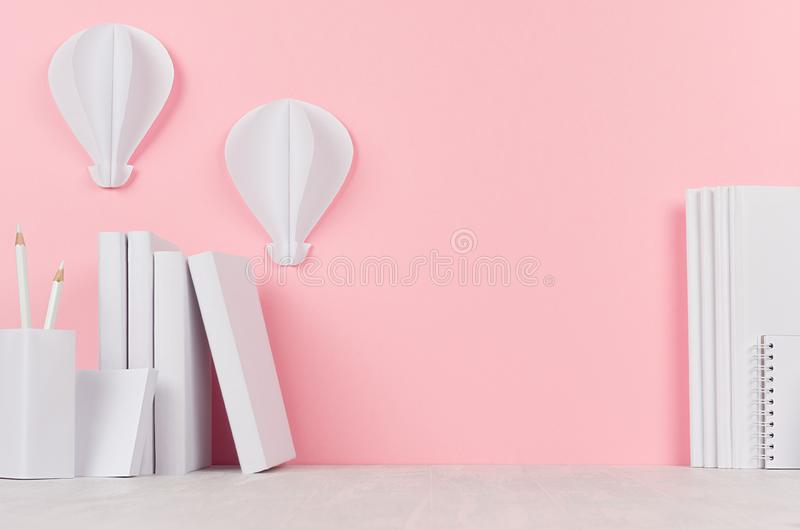 Creative back to school background - white books, stationery and hot air balloons origami on soft pink backdrop. royalty free stock photo