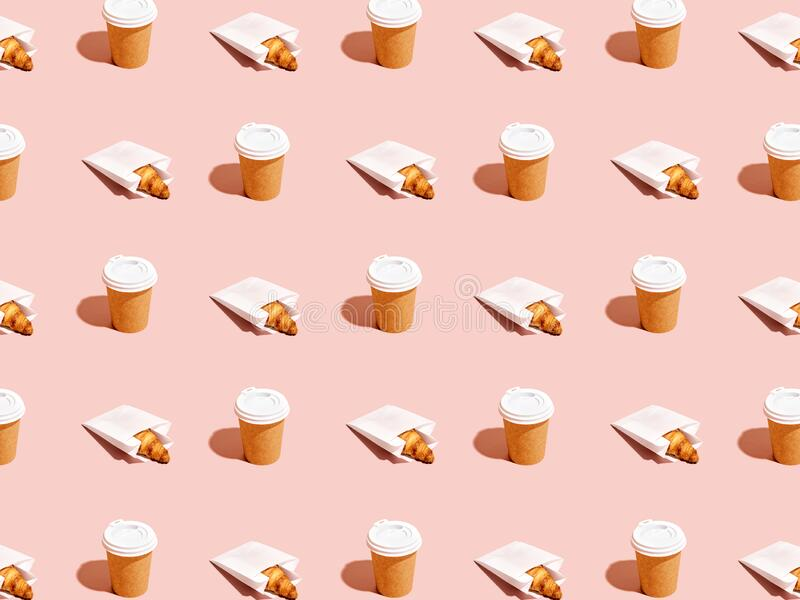 Creative background for breakfast to go. Pattern of packaged croissants and craft paper disposable cups on pink background. Takeout food abstract background royalty free stock photography