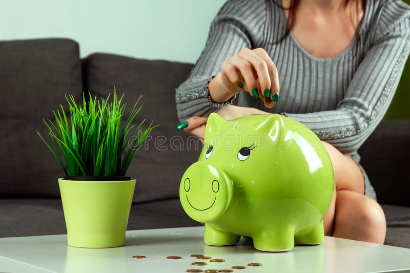 Creative background, close-up girl`s hand, throws a coin into the piggy bank in the form of a green pig. The concept of saving royalty free stock photo