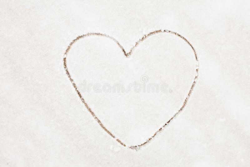 Outline Heart drawn on a white snow Background stock photos
