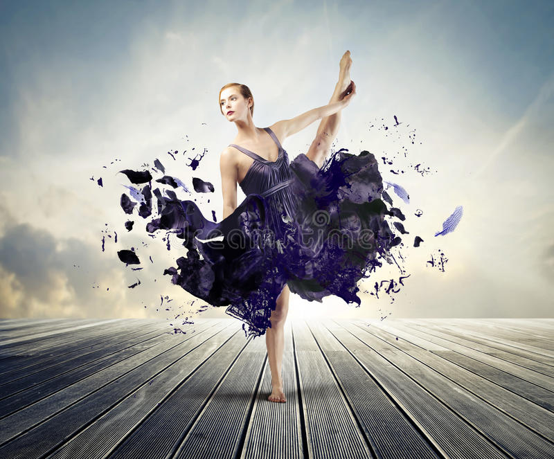 Creative ballet. Beautiful ballerina dancing on a wood floor with her dress melting away royalty free stock photography