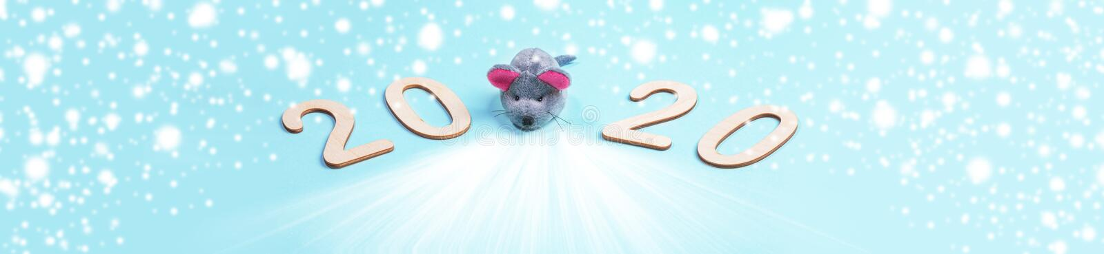 Creative banner of 2020 Merry Christmas or Happy new year. Wooden numbers with grey toy rat on snowy blue backdrop stock photo