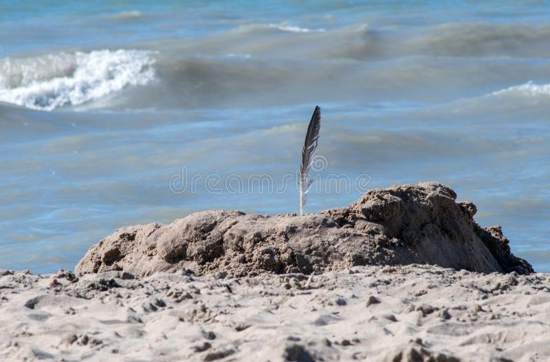 Creative beach castle topped with a feather royalty free stock photography