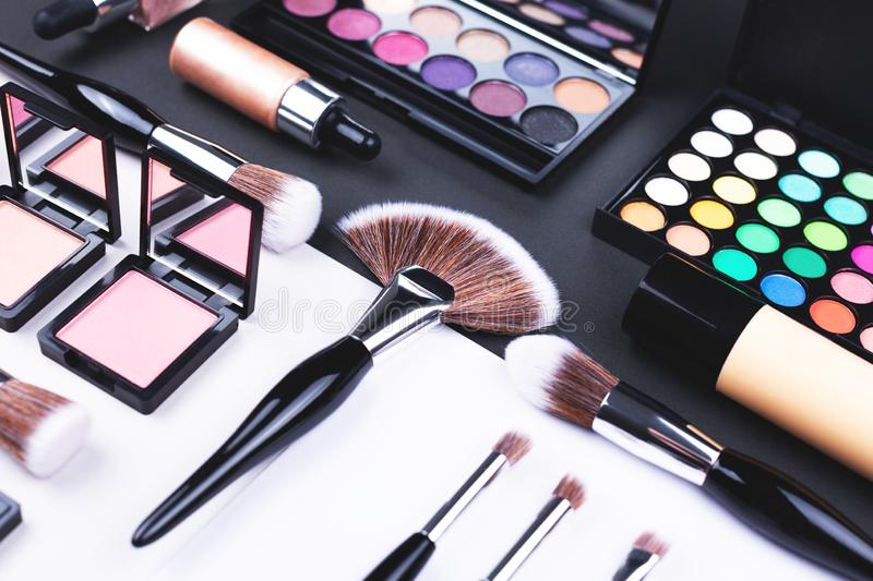 Creative beauty and makeup flat lay made with brushes, foundation, eye shadows and blush stock images