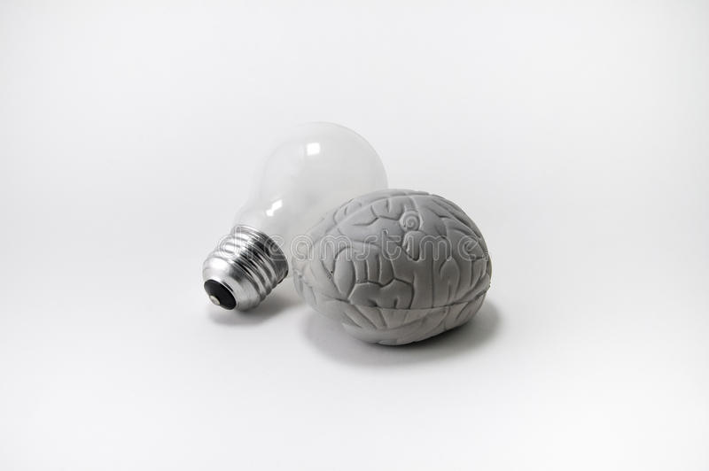 Creative brain and light bulb - idea!. A toy in the shape of a human brain is positioned next to an incandescent light bulb symbolizing an idea stock photos