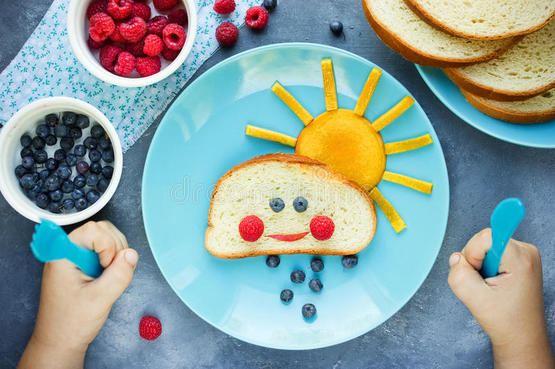 Creative breakfast idea for kids - bread bun with fruit and berry shaped funny cloud with peach sun and blueberry rain. Fun with food royalty free stock images