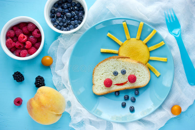 Creative breakfast idea for kids - bread bun with fruit and berry shaped funny cloud with peach sun and blueberry rain , fun with stock images