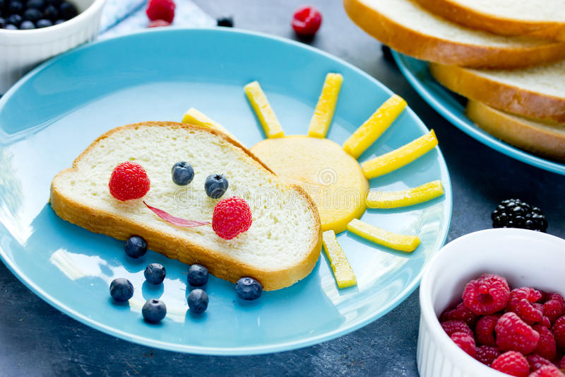 Creative breakfast idea for kids - bread bun with fruit and berry shaped funny cloud with peach sun and blueberry rain. Fun with food royalty free stock photos