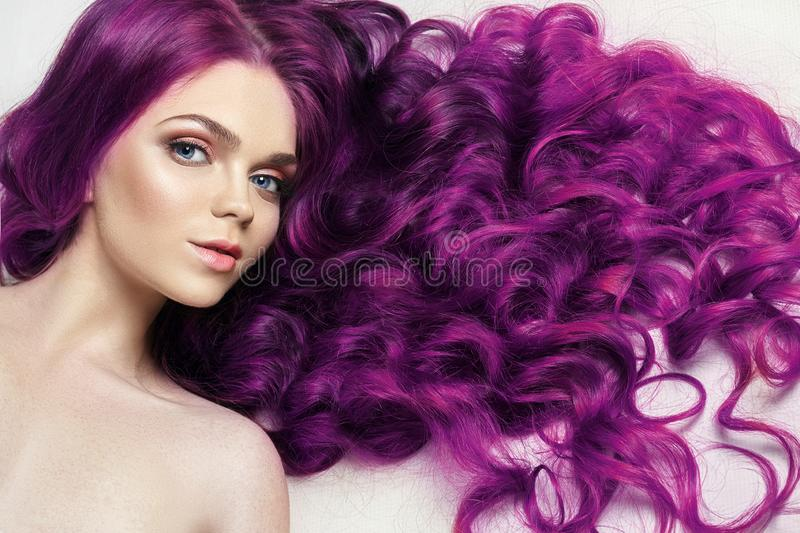 Creative bright coloring of a woman`s hair, careful care of the hair roots. Bright dye for coloring, long strong hair. Natural stock photography
