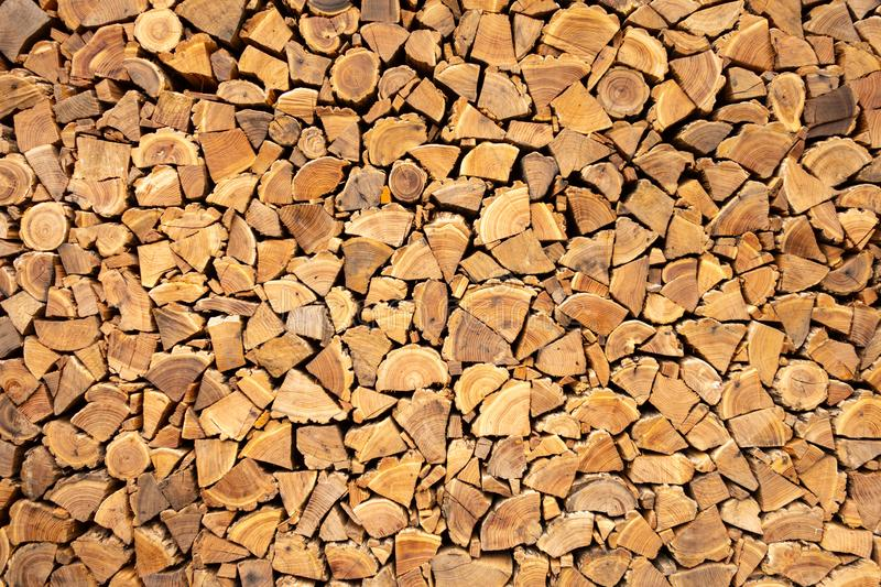 Creative brown background of neatly stacked firewood. Brown texture of natural wood. royalty free stock photo