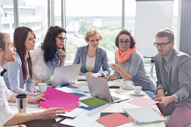 Creative business colleagues analyzing photographs at conference table in office royalty free stock photos