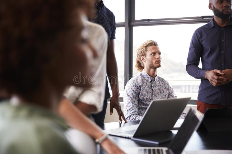 Creative business colleagues listening to presentation in a meeting room, close up, selective focus stock photos