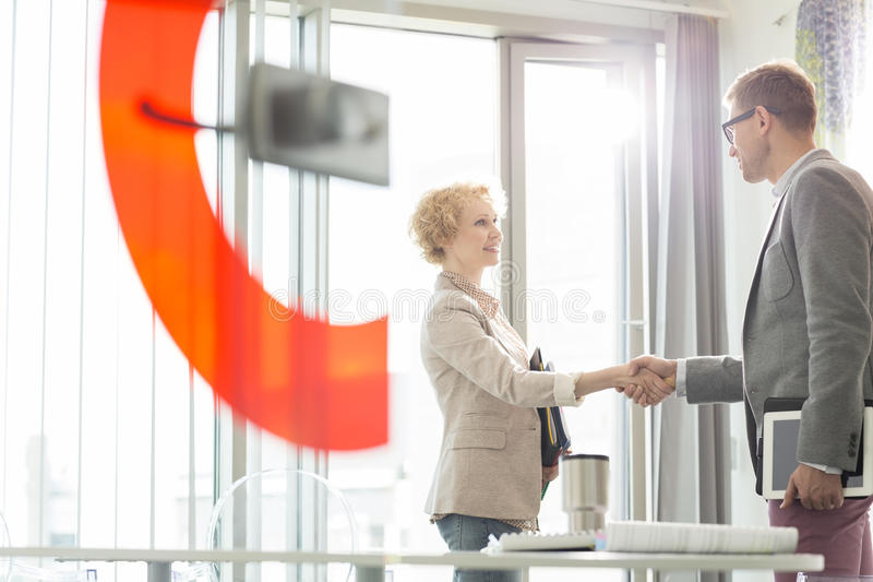 Creative business colleagues shaking hands in office royalty free stock image