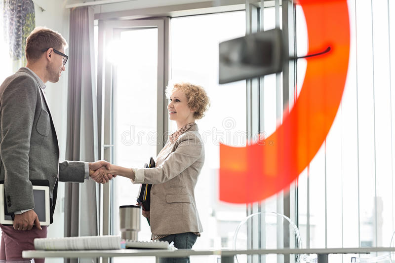 Creative business colleagues shaking hands in office stock images