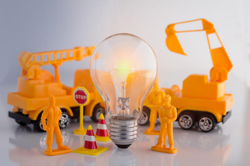 Creative business concept with light bulb and workmen figure. And truck toys royalty free stock image