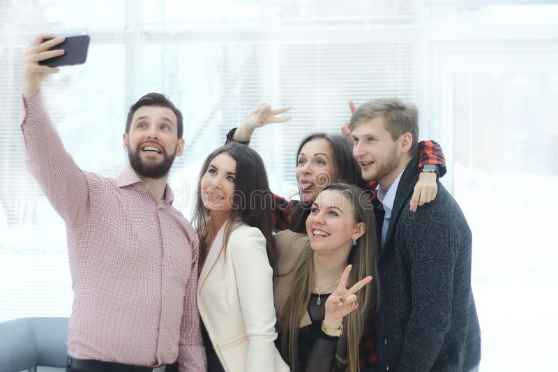 Creative business group takes selfies in a modern office royalty free stock photography