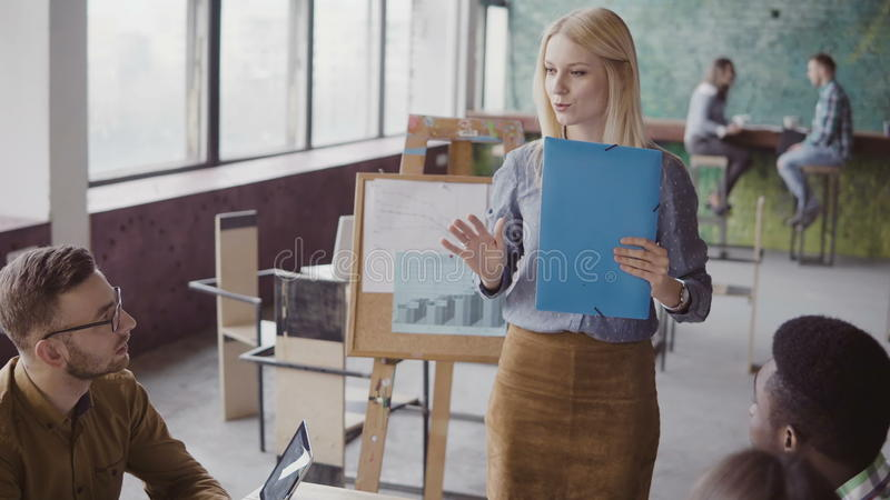 Creative business meeting of mixed race team. Woman team leader presenting to group of people new idea at modern office. stock photo
