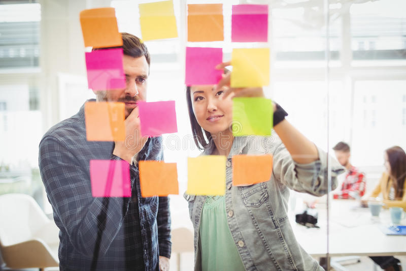 Creative business people looking at multi colored sticky notes on glass. In meeting room at creative office royalty free stock image