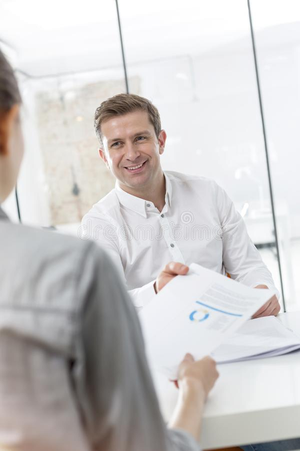 Creative businessman giving document to colleague in office royalty free stock photos