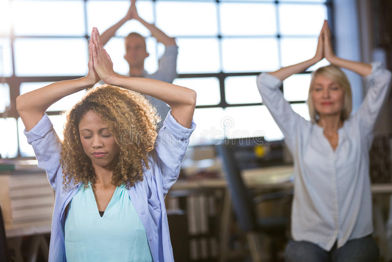 Creative business people practicing yoga stock photo