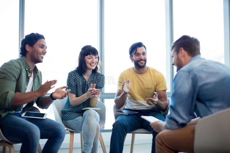 Creative business team applauding for their colleague in office royalty free stock image