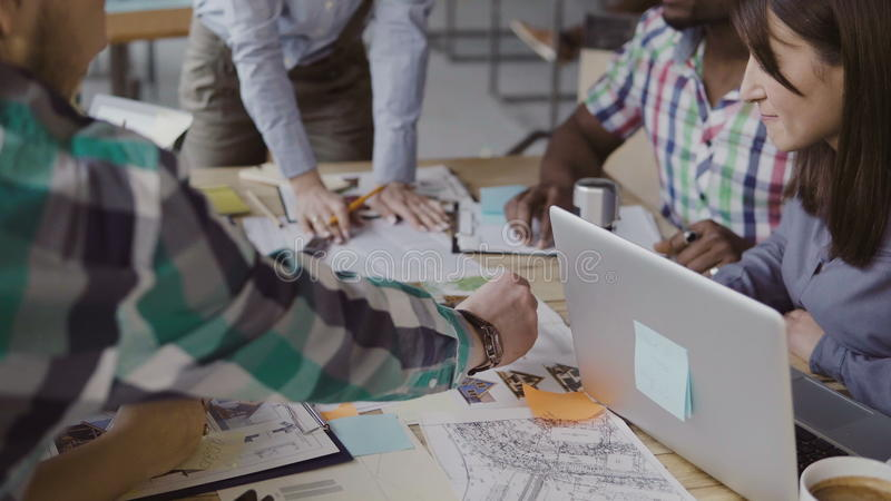 Creative business team discussing architectural project. Brainstorming of mixed race group of people in trendy office. stock photo