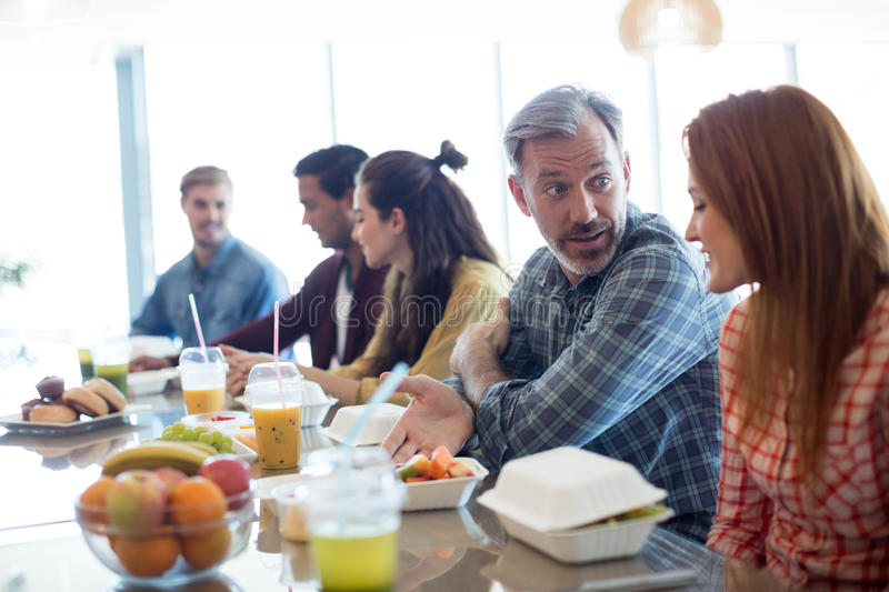 Creative business team discussing while having meal royalty free stock photo