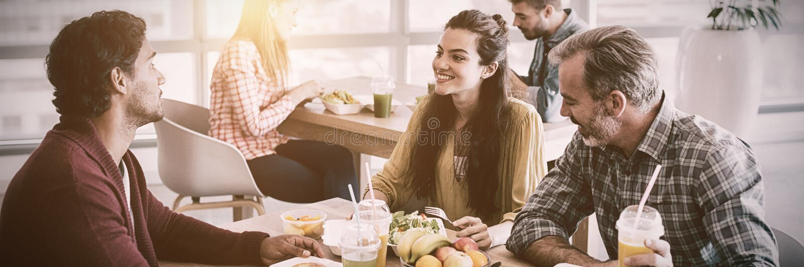 Creative business team discussing while having meal stock photos