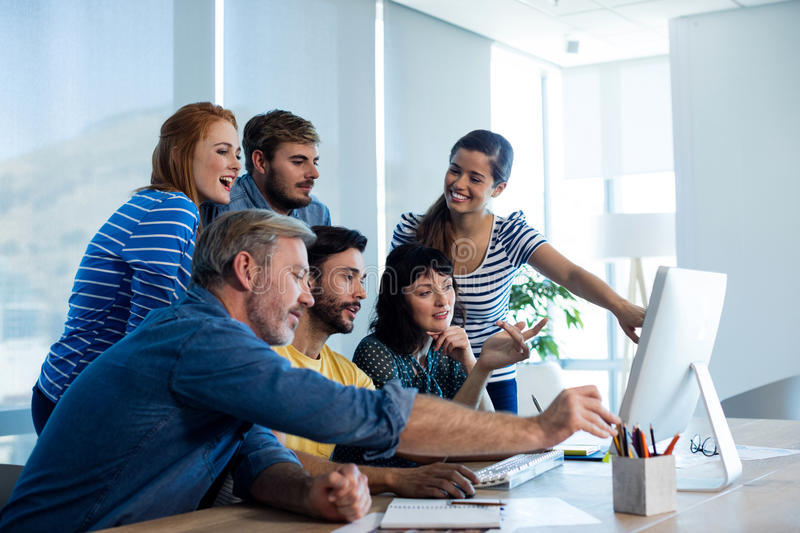 Creative business team discussing while working together on desktop pc in office stock image